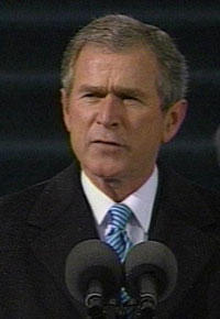 President George Bush pauses for a moment during a press conference to make a serious facial expression.